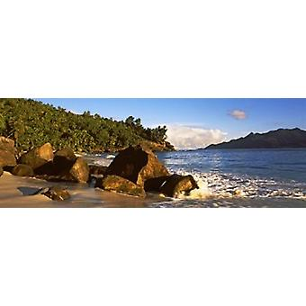 Waves splashing onto rocks on North Island with Silhouette Island in the background Seychelles Poster Print