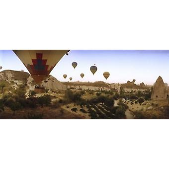 Hot air balloons over landscape at sunrise Cappadocia Central Anatolia Region Turkey Poster Print
