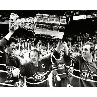 Yvan Cournoyer #12  hoist the Stanley Cup Trophy with help from teammates Yvon Lambert #10 and Guy Lafleur #10 of the Montreal Canadiens after defeating the Boston Bruins at the Boston Garden on May 2