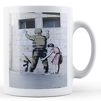 Printed mug featuring Banksy's, 'Girl Frisking Soldier' artwork